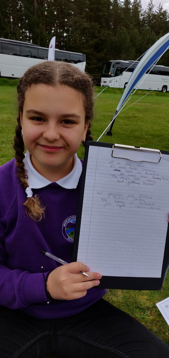 Schoolgirl shows her poem in Polish and English on a clipboard