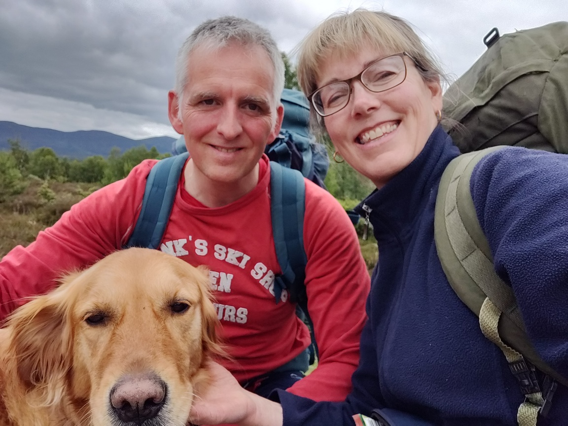 Man & woman with backpacks and dog