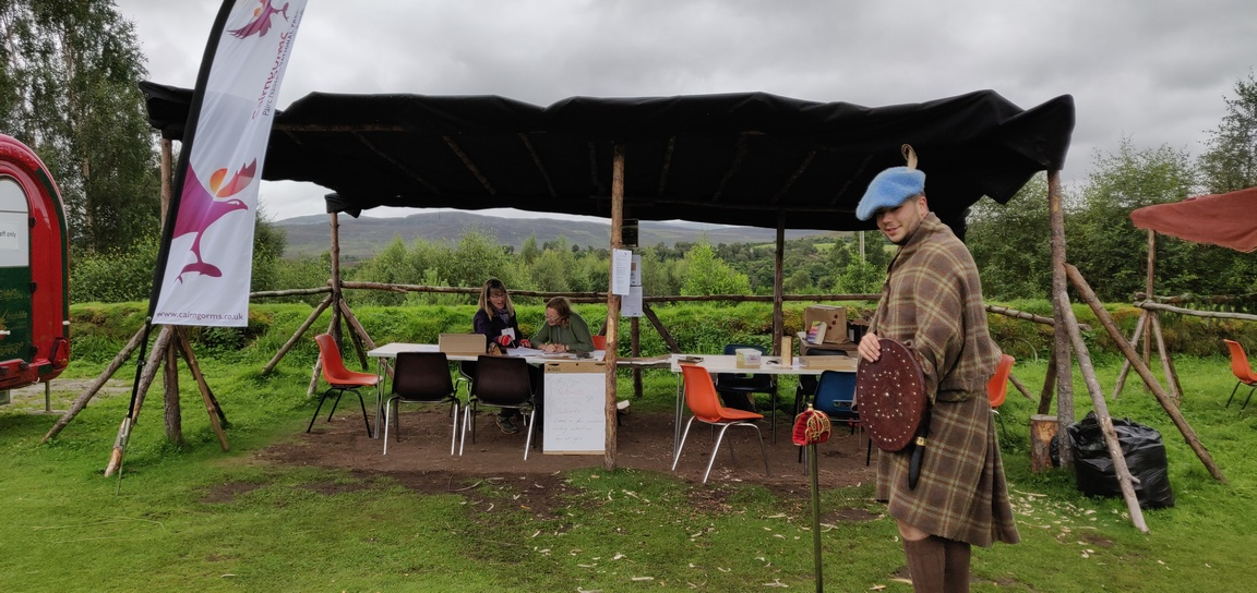 Shelter with tables, Cairngorms National Park sign and man in Highland dress