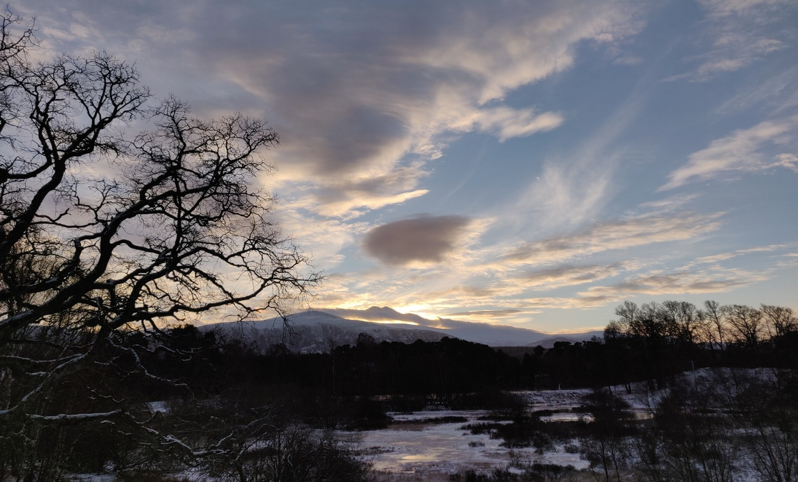 Winter landscape at dawn, snowy hill, frozen loch, dark trees, sun rising behind clouds.