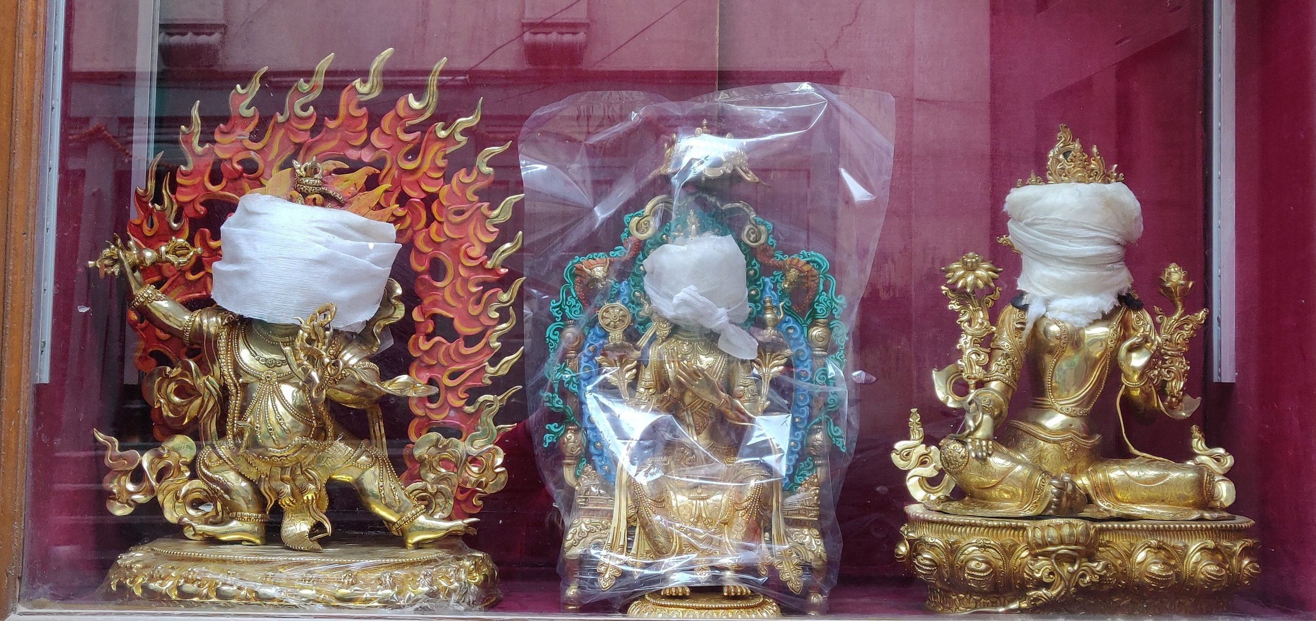 three gold idols with faces wrapped in cloth